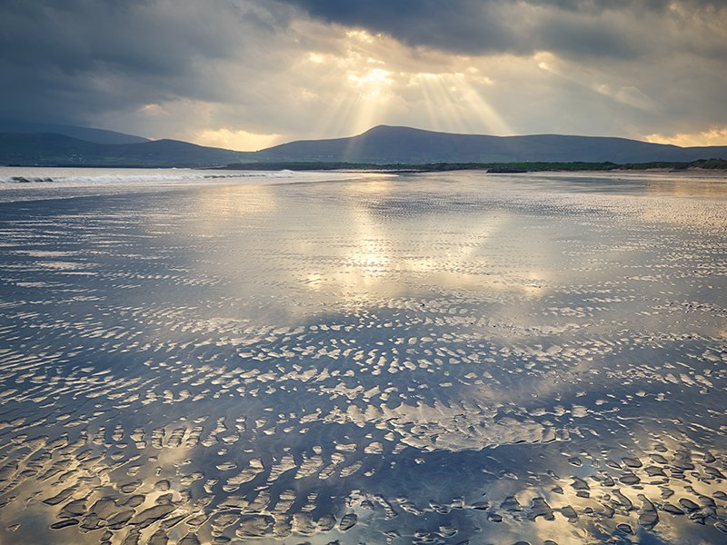 On an early stormy morning, sunrise rays penetrate through the dark sky over Rinn Chonaill mountain. The low tide mirrors the sunrise light with reflecting sand patterns. Smerwick Harbor, Dingle Peninsula, County Kerry, Ireland.