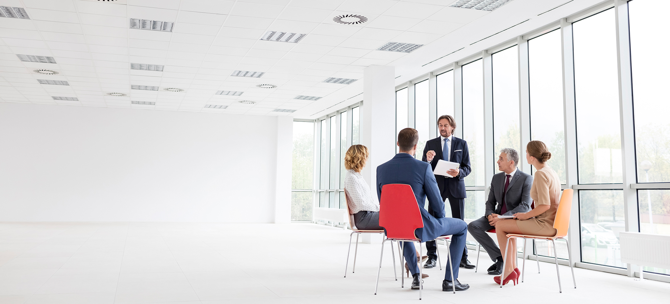 businessman talking to colleagues sitting in circle in empty office