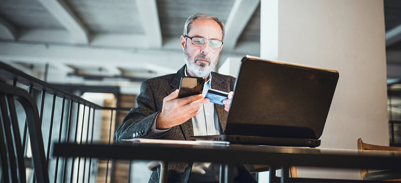 senior businessman with beard making credit card purchase