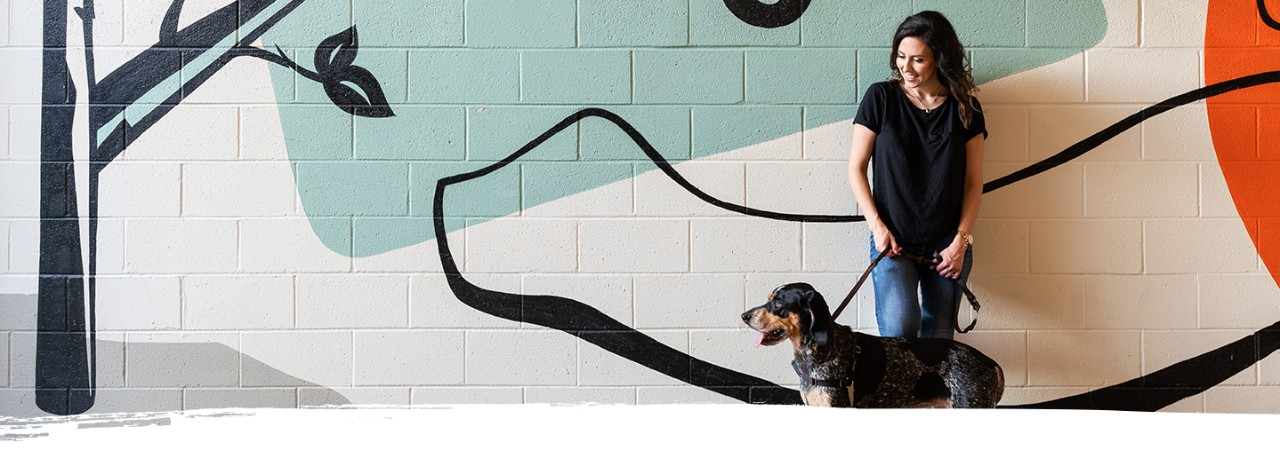A woman enjoys a mural with her dog in Atlanta's Ponce City Market
