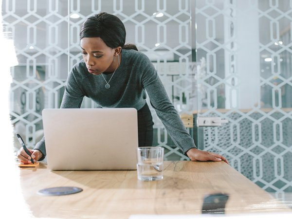 woman working on laptop at home office desk