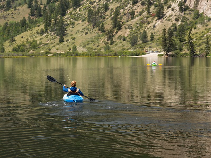Kayaking on Cottonwood lake in the valley on clear calm day with the lake stretching off to distance