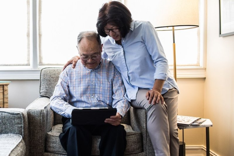 Senior citizens reading from a tablet