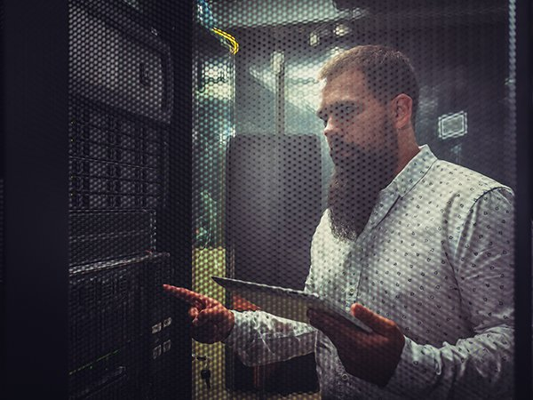 Young IT engineer inspecting data center servers