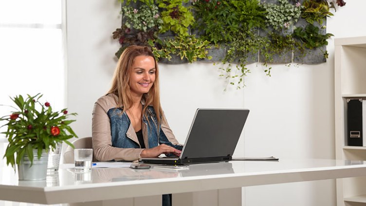 Female at a laptop computer in a room full of plants.